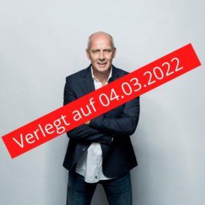 Bario Basler vor grau weisem Hintergrund verschränkt die Arme und schaut in die Kamera. Darüber ein roter Balken mit dem Schriftzug Verlegt auf 04.03.2022