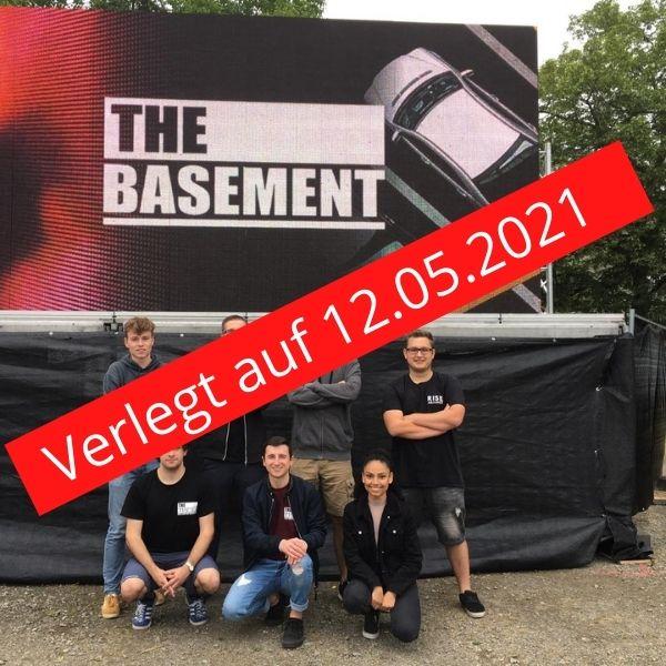 Die Coverband Basement posiert vor einem Plakat. Darüber ein roter Balken mit dem Schriftzug Verlegt auf 12.05.2021