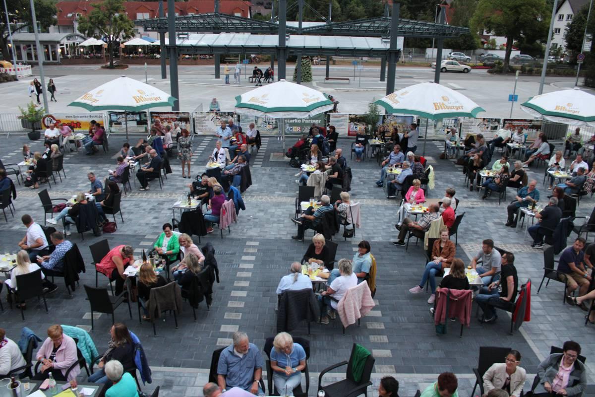 Blick von oben auf die Bestuhlung der Ramsteiner Sommer Lounge. Mehrere Tischgruppen mit Gästen