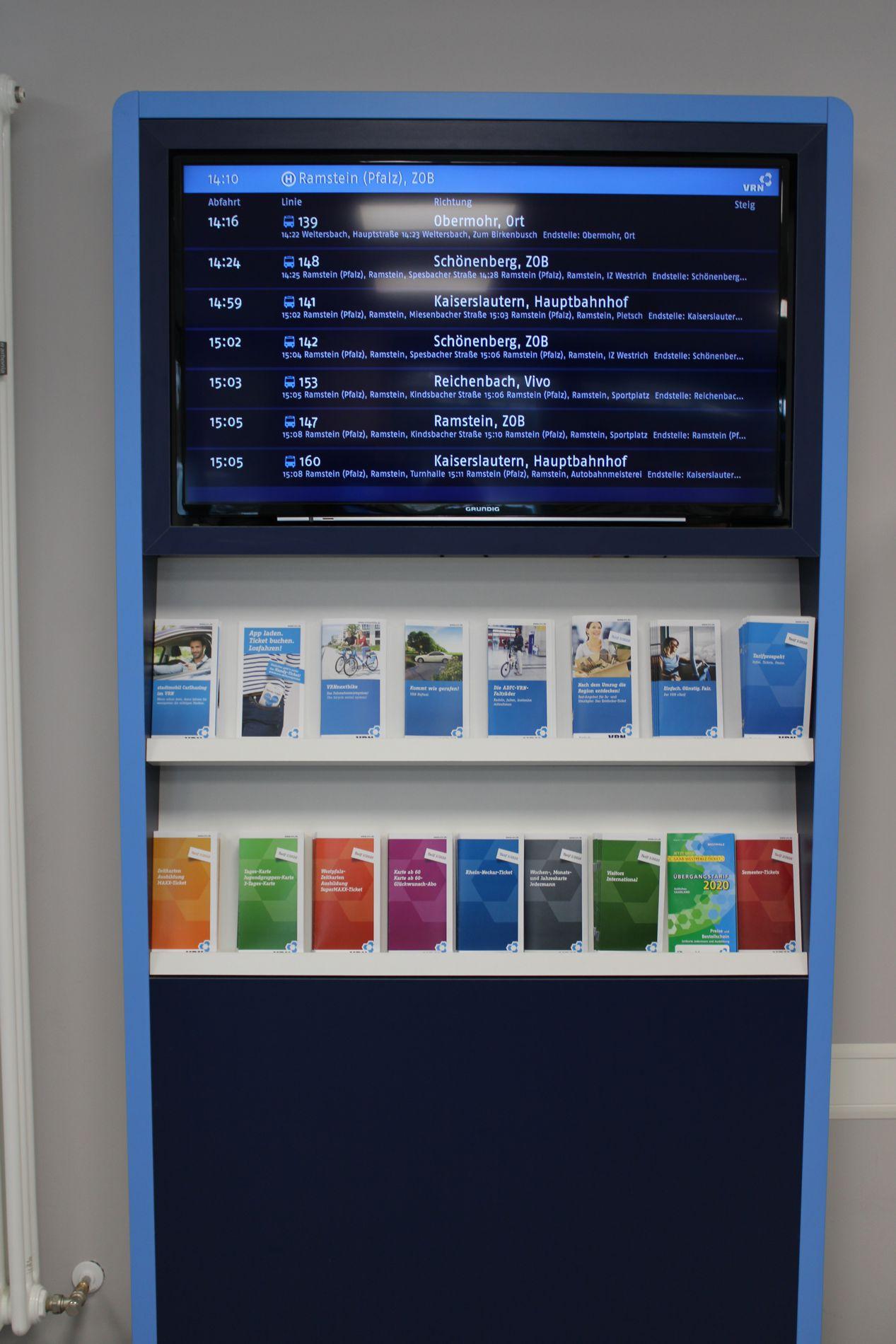 Monitor mit Abfahrtszeiten der Busse in Ramstein und darunter verschiedene Flyer vom VRN in der Mobilitätszentrale in Ramstein