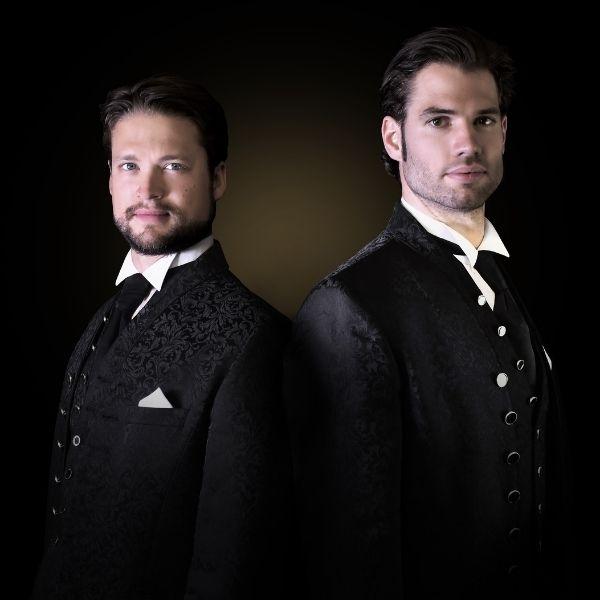 Die beiden Magier von Golden Ace mit Anzügen gekleidet posieren für die Kamera