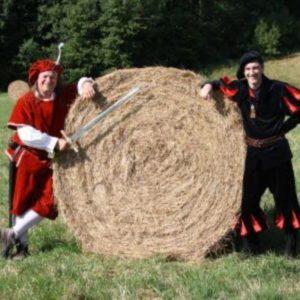 Die beiden Schauspieler vom Rittermahl in Kostümen auf einer Wiese neben einem Heuballen